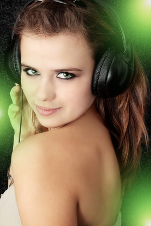 Beautiful young  women listening music in headphones  Stock Photo - 8403270