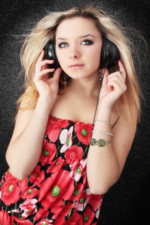 Young beautiful blond listens to the music photo