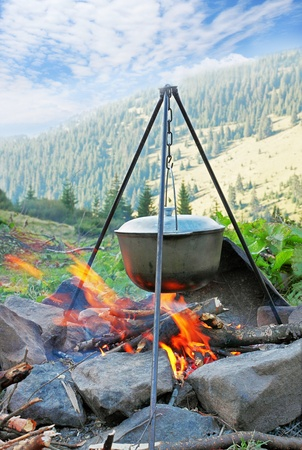 Preparation of food in the large kettle on nature Stock Photo - 8874808