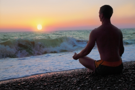 Man in the meditation on the shore of the sea  photo