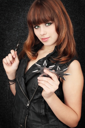Beautiful girl holds in the hands of shuriken  photo