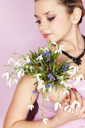 Beautiful young girl with the bouquet of the snowdrops photo