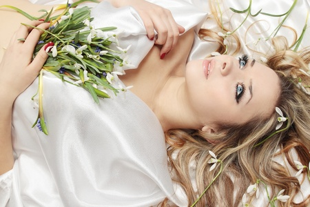 Beautiful blond lies on the white into the flowers Archivio Fotografico