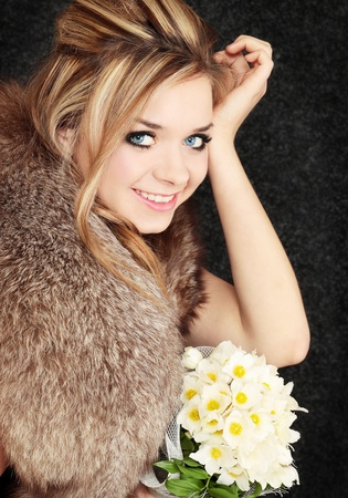 young beautiful blond in the fur with the bouquet photo