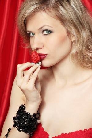 Young beautiful sexual blond eats the strawberries Stock Photo - 9523592