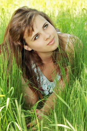 beautiful dreamy girl lies at the grass photo