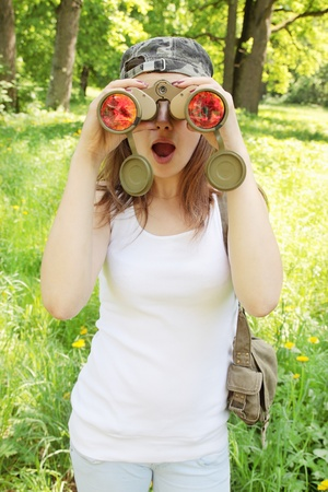 observes: young girl observes wonder into the binoculars Stock Photo