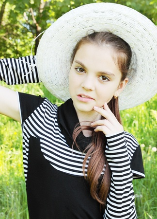 portrait is young girl in the hat on nature photo