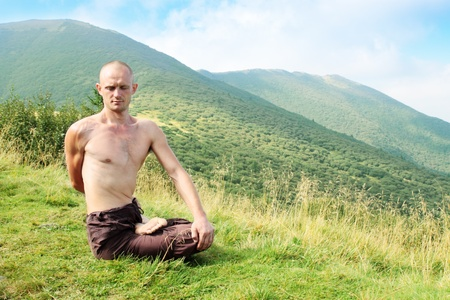 Young man is occupied yogi in the foot of the mountains photo