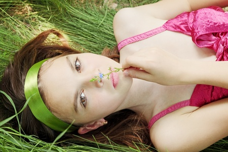 Young beautiful girl lies and smells the flower photo