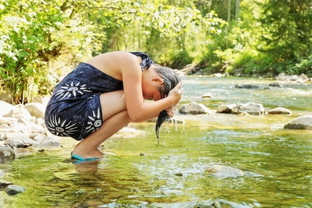 beautiful girl washes head in the mountain stream photo