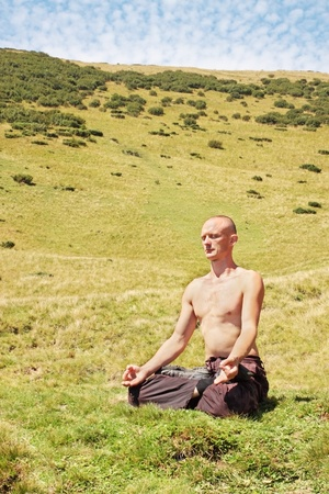 Man meditating at the foot of the mountain photo