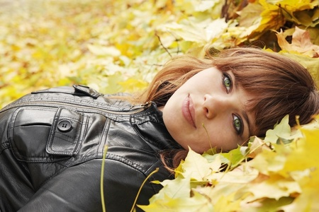 beautiful girl lies on yellow maple leaves Archivio Fotografico