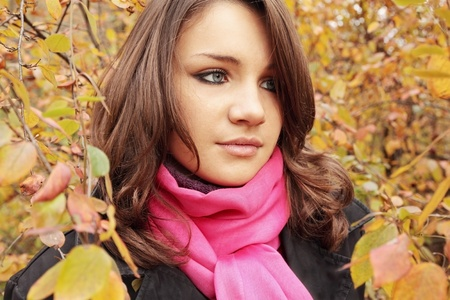 beautiful girl pensive looks at autumnal leaves Stock Photo - 10850679
