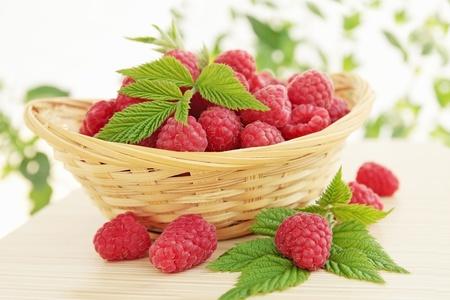 cesta de frutas: frambuesa fresca es jugosa en la canasta tejida