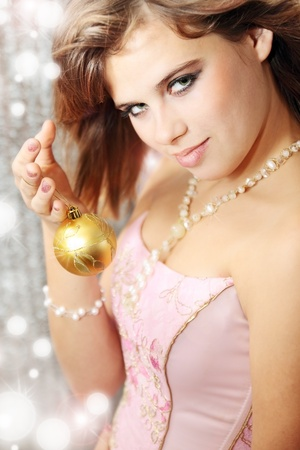 Beautiful young woman holds the new-year ball photo