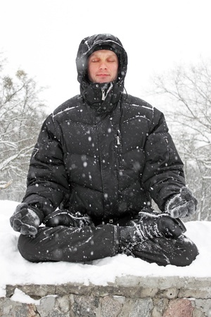 man meditating in lotus position in winter