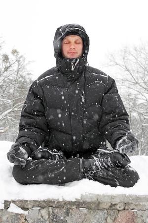 man meditating in lotus position in winter
