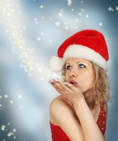 woman in the cap Santa Claus blows to the snowflakes photo