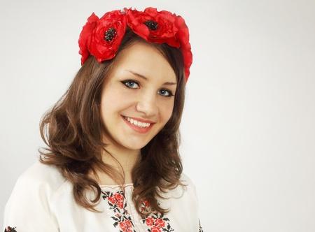Beautiful, friendly Ukrainian in a wreath of poppies photo