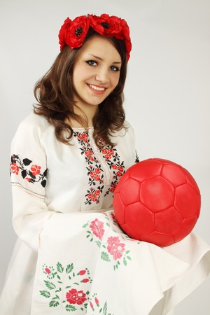 Ukrainian woman it invites on the Euro2012; holds red ball on embroidered towel photo