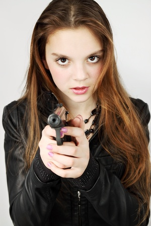 Young beautiful girl holds in the hand the weapon Stock Photo - 12939901
