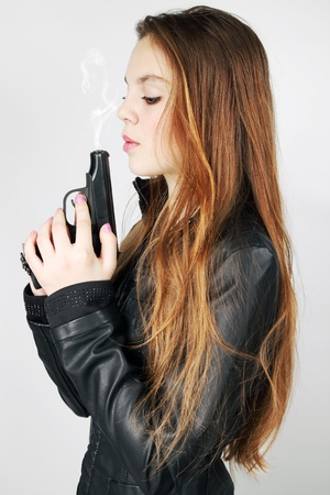 girl blows to the smoke in the pistol photo