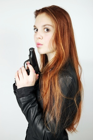 woman with the long red hair holds the pistol  Stock Photo