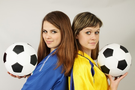 two beautiful football fans hold the balls photo