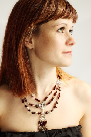Beautiful red-haired woman in the garnet necklace photo