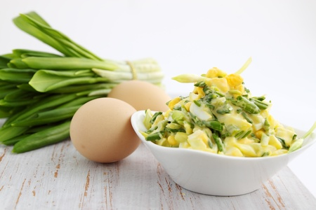 salad with ramson and eggs on a wooden board Stock Photo