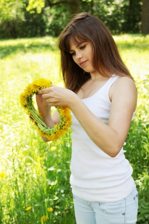 Beautiful young woman weaves a wreath of dandelions Stock Photo - 13606706
