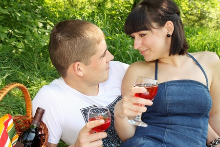 Young couple with glasses of wine looking at each other photo