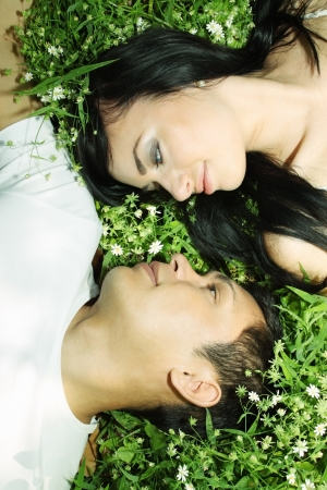 Young couple lying on grass face to face Stock Photo - 13606802