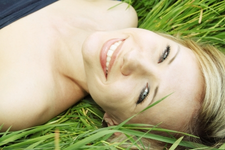 smiling woman was lying on the grass photo