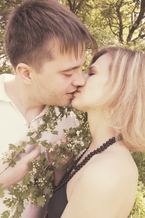 Young couple kissing near the blooming hawthorn photo