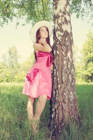 Dreamy girl in a hat standing near a birch