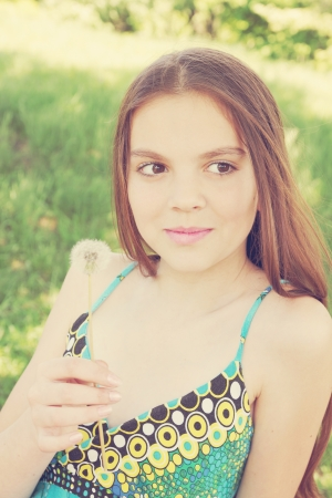 beautiful girl in sarafan holding a dandelion photo
