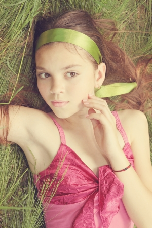 Young woman in pink sarafan lying on the grass photo