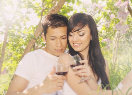 young couple drinking wine under the lilac bush photo