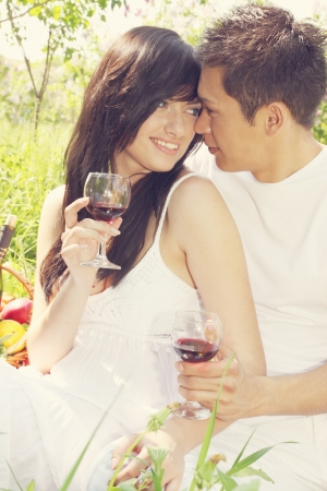 Young couple drinking wine and looking at each other photo
