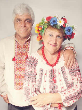 An elderly man hugs a woman. Couple in Ukrainian costumes photo