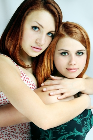 Two red-haired young women hugging each other photo