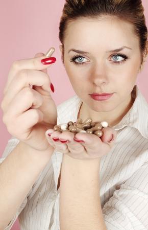 pills in hand: Mujer joven mirando a las pastillas en la mano