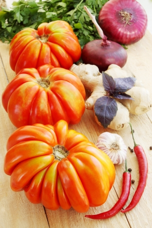 Large tomatoes with spices, vegetable still life photo