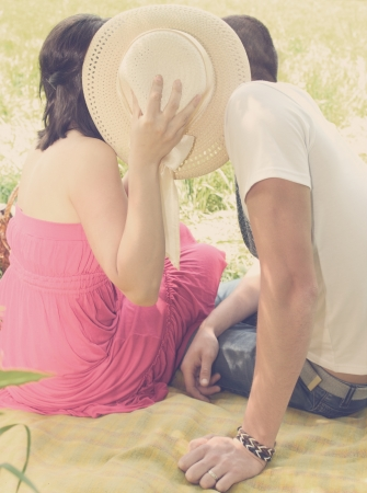 A young couple kissing having covered hat Stock Photo - 14903787