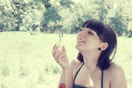 Young woman blow bubbles in the meadow photo