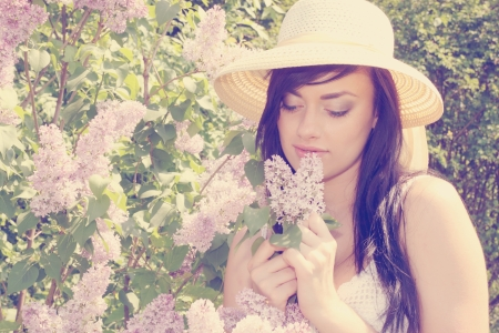 A beautiful young woman smelling a blooming lilac bush photo