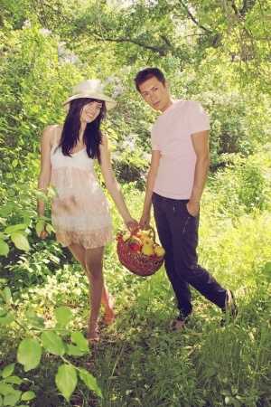 young couple have a fruit basket in the garden photo