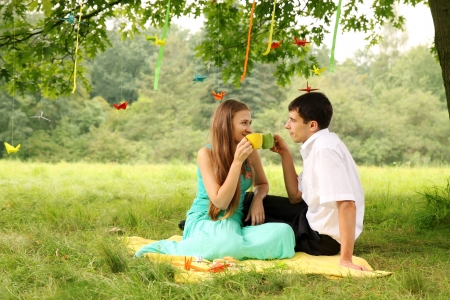 Young couple drinking tea in the park photo